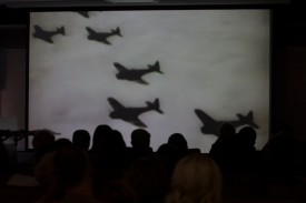 WWII enthusiasts watch archival footage of fighter planes.