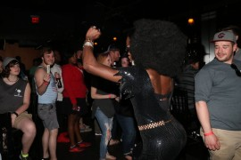 Symone Bishop dances during her number while bar patrons look on.