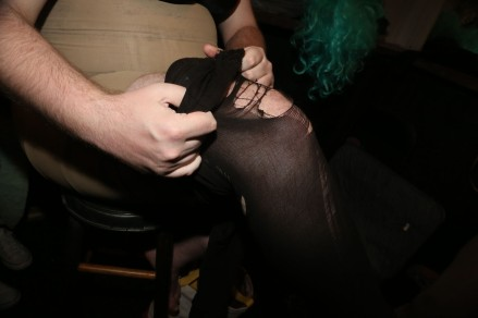 After her makeup is done, Ebony pulls up her ripped black tights.