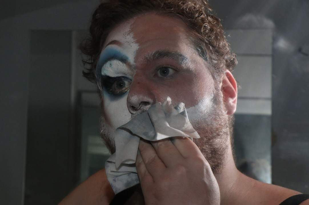 Caleb Coker removes their makeup with several face wipes after a show.
